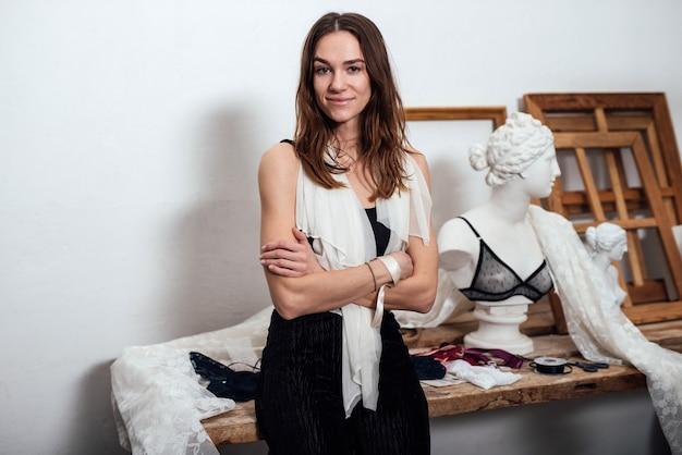 Дизайнер нижнего белья женщина в ее мастерской за ее столом.