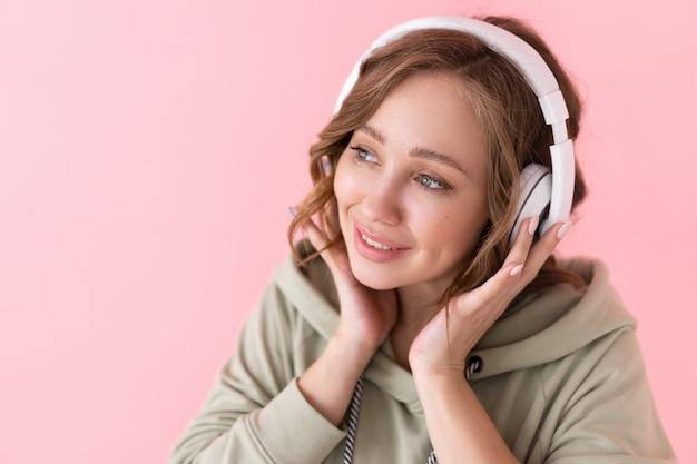 여자 들어 음악 헤드폰 백인 여성 특대 까마귀 분홍색 배경을 입고 팟 캐스트 또는 오디오 책을 즐길 수