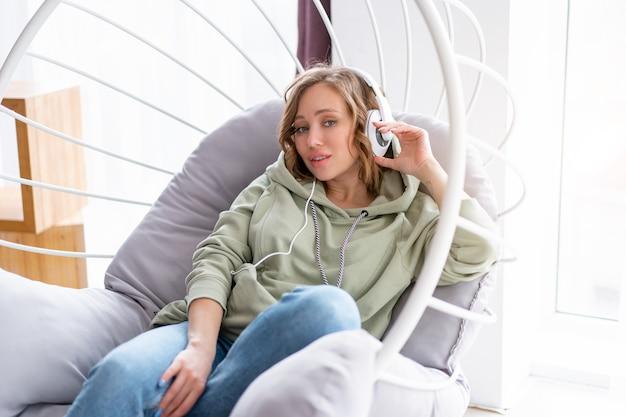 여자 들어 음악 헤드폰 백인 여성 로프트 디자인 의자에서 휴식하는 동안 팟 캐스트 또는 오디오 북을 즐길 수