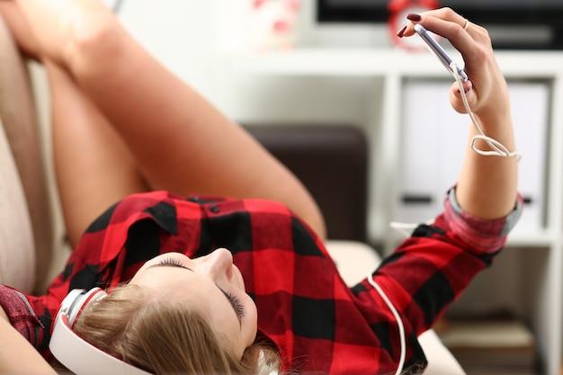 Женщина слушать музыку лежит на диване