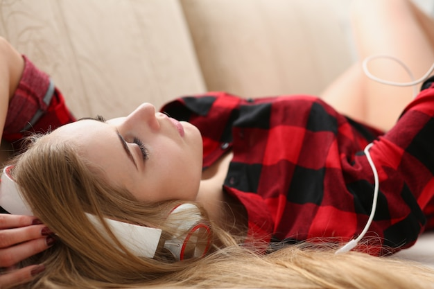 Woman listen music lie on sofa