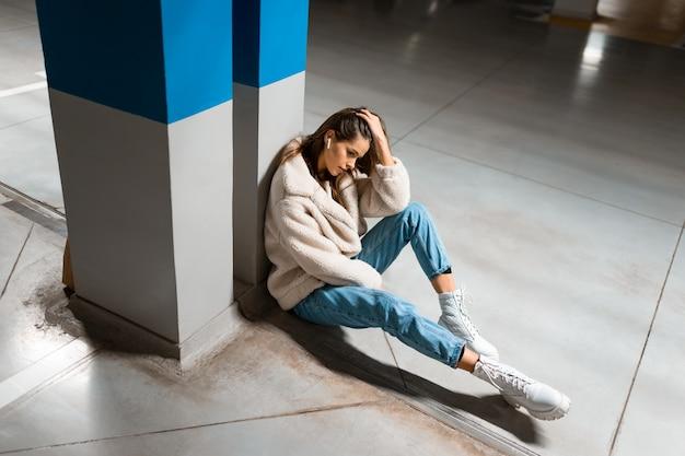 女性は地下駐車場で音楽を聴く