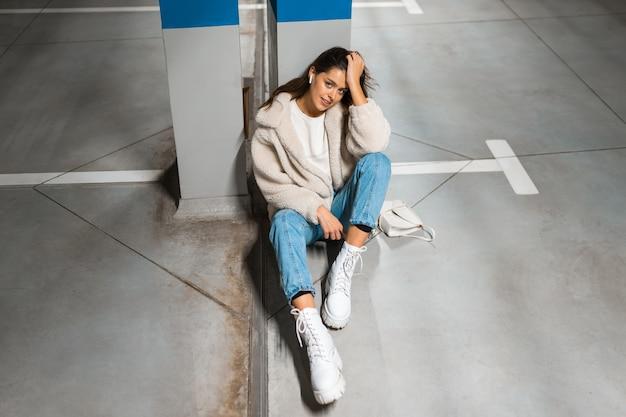 여자는 지하 주차장에서 음악을 듣습니다.