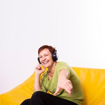 Женщина слушает музыку и смотрит на фотографа