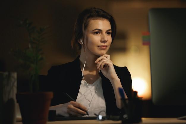 Женщина слушает музыку и работает