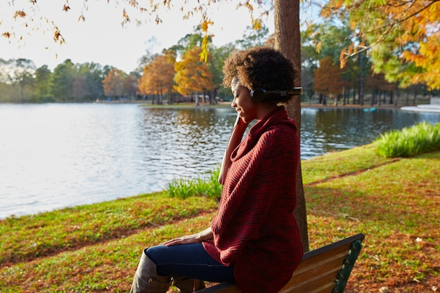 Woman listening music in the autumn park