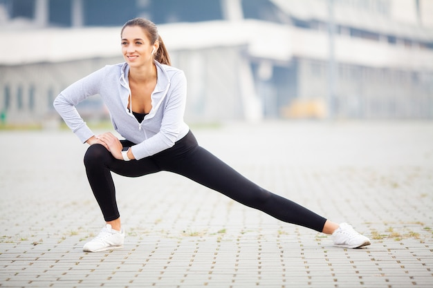 Woman listening music, doing workout exercises on street
