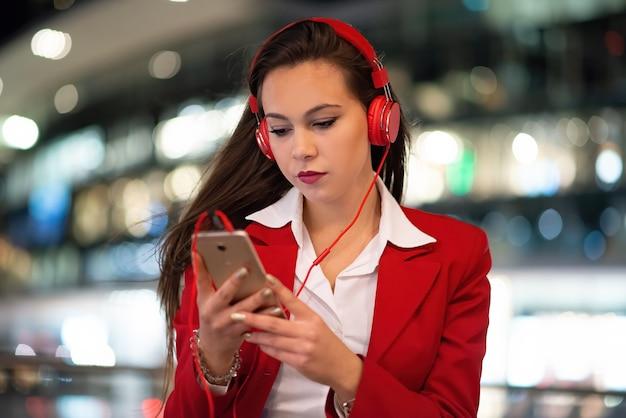 携帯電話から音楽を聴いている女性