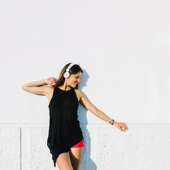 Woman listening to music on headphone standing in front of wall
