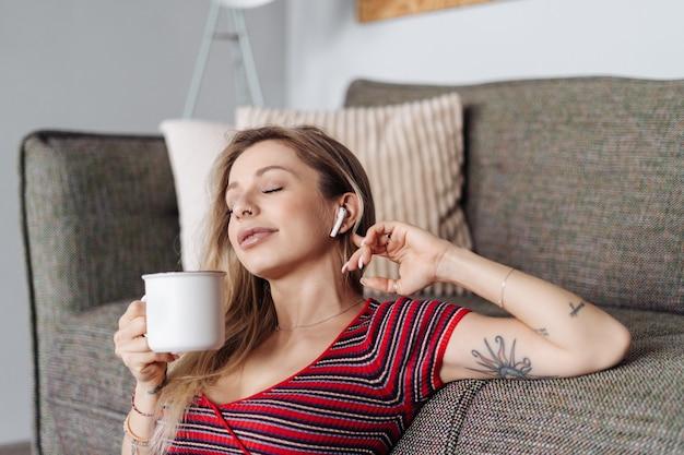 차를 마시는 거실에서 소파 근처에 앉아있는 동안 헤드폰에서 여자 듣기 음악