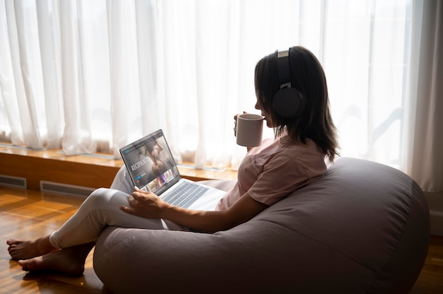 Donna che ascolta la musica tramite le cuffie a casa