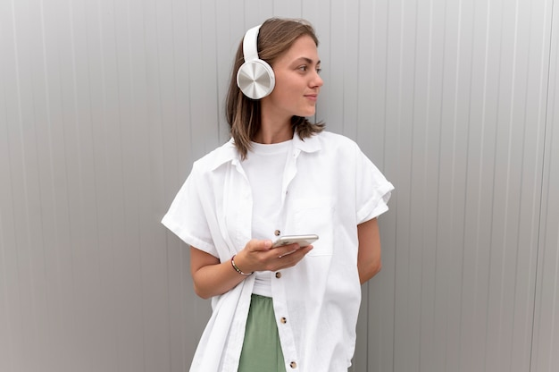 Woman listening to music through her headphones while holding her smartphone
