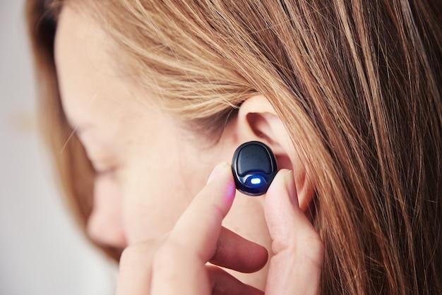 ワイヤレスイヤホンで音楽を聴く女性。耳にbluetoothヘッドホーンを使用している白人女性、クローズアップ