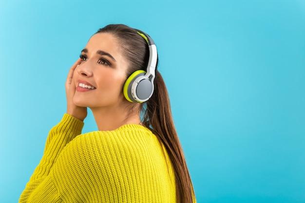 Donna che ascolta la musica in cuffie senza fili felice che indossa un maglione lavorato a maglia giallo in posa sul blu