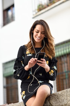 Woman listening to the music with earphones and smart phone outdoors.