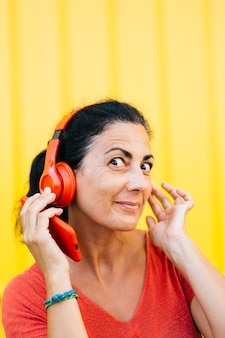 Woman listening music with red headphones against a yellow background