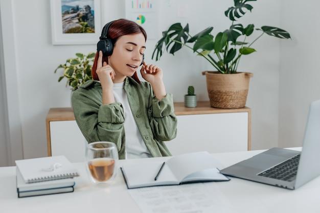 Женщина, слушающая музыку с беспроводными наушниками концепция отдыха во время работы счастливая девушка поет