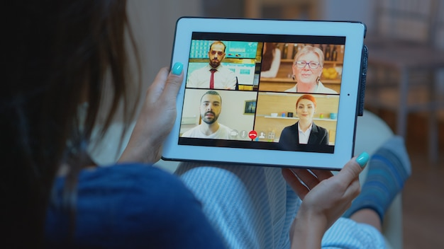 Woman listening online training on tablet late at night sitting on sofa. remote worker having virtual meeting consulting with colleagues on videocall and webcam chat using internet technology.