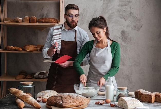 パンのレシピを聞いて料理する女性