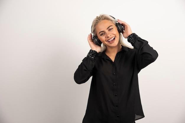 흰색 바탕에 헤드폰으로 여자 듣기 노래입니다. 고품질 사진