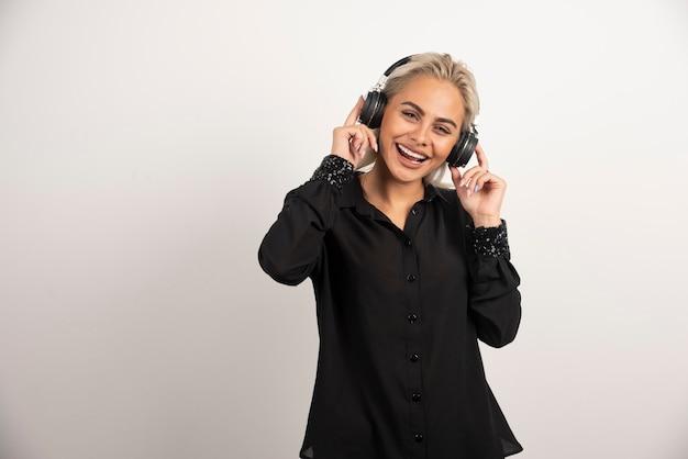 Canzone d'ascolto della donna con le cuffie su priorità bassa bianca. foto di alta qualità