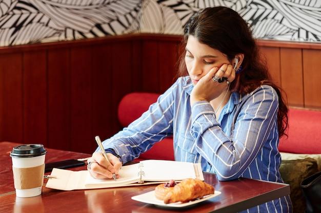 Женщина слушает лекцию и делает заметки