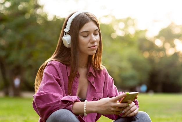 Женщина слушает музыку и смотрит на свой телефон