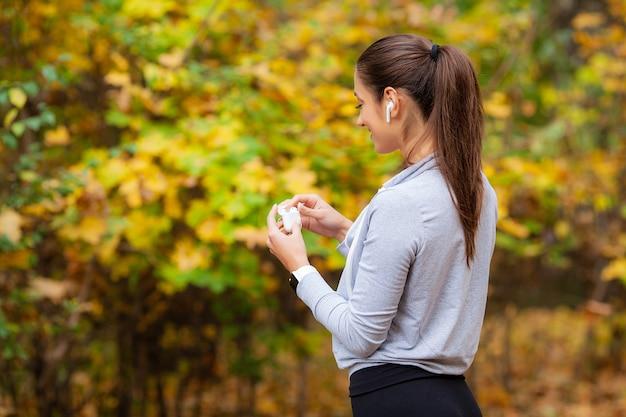 Женщина слушает музыку и работает в парке