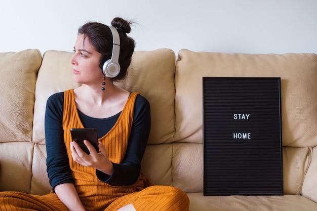 女性が自宅でヘッドフォンで音楽を聴きます。自宅のソファでコロナウイルス感染した人。家にいる。パンデミックウイルス病covid 19。