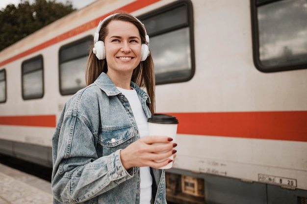 Женщина слушает музыку на платформе поезда