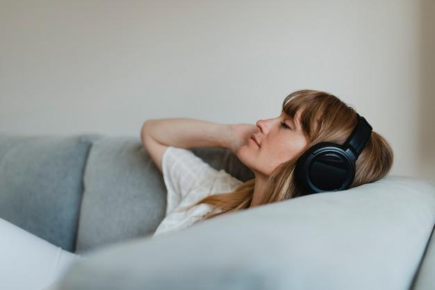 Женщина слушает музыку во время карантина из-за коронавируса на диване