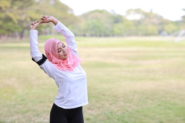 屋外で運動しながらワイヤレスイヤホンや携帯電話から音楽を聴いている女性