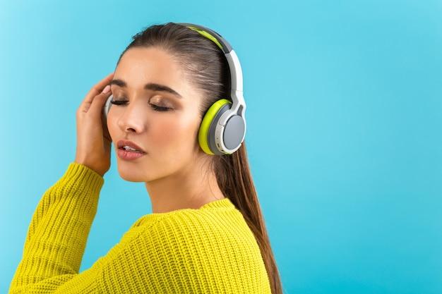 青でポーズをとって黄色のニットセーターを着て幸せなワイヤレスヘッドフォンで音楽を聴いている女性