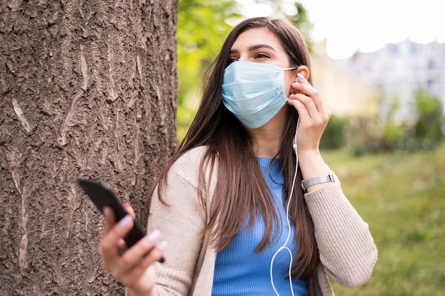 Женщина слушает музыку на наушники во время ношения медицинской маски