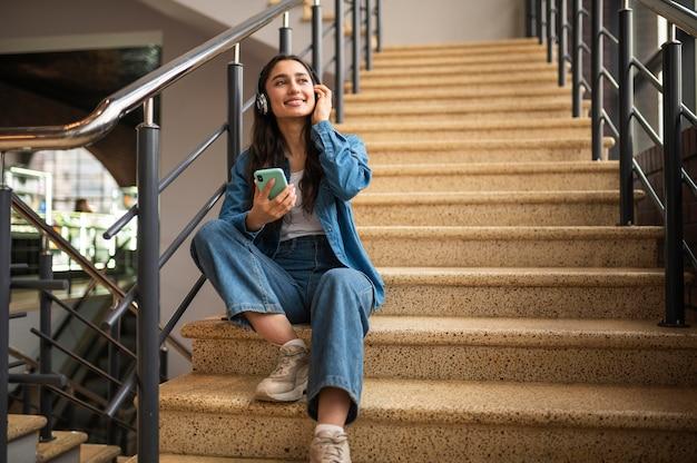 Женщина слушает музыку в наушниках, сидя на лестнице
