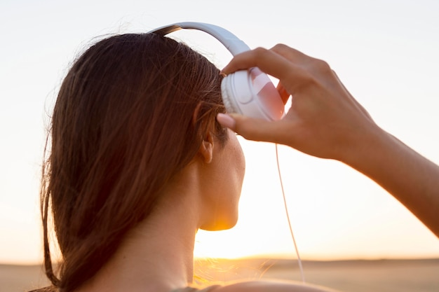 Женщина слушает музыку в наушниках, любуясь закатом