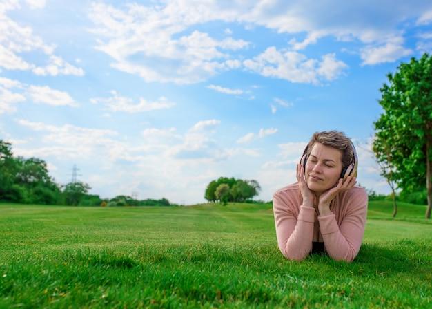 音楽やオーディオブックを聴く女性と公園で日当たりの良い春の暖かい日に牧草地/緑の芝生で休む