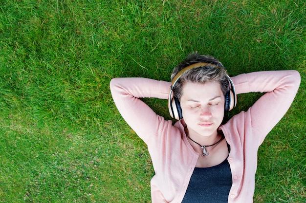音楽やオーディオブックを聞いて、緑の芝生で休んでいる女性
