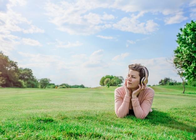 音楽やオーディオブックを聞いて、公園の草原で休んでいる女性
