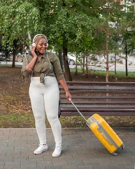 Женщина слушает музыку через наушники, заботясь о своем багаже