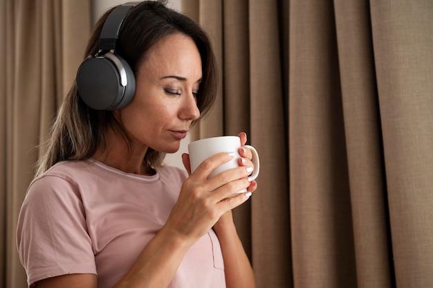 Женщина, слушающая музыку через наушники дома