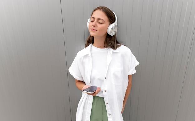 Женщина слушает музыку через наушники, держа в руке смартфон