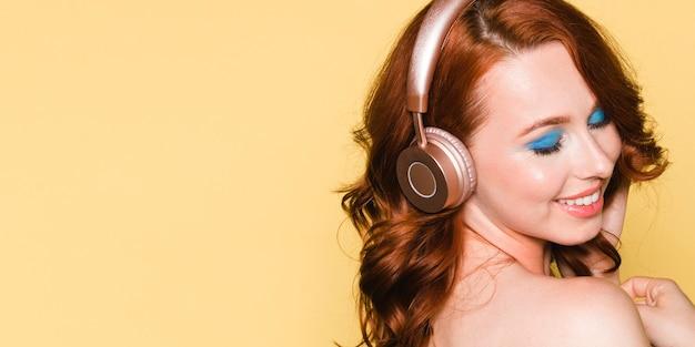 ヘッドフォンで音楽を聴いている女性