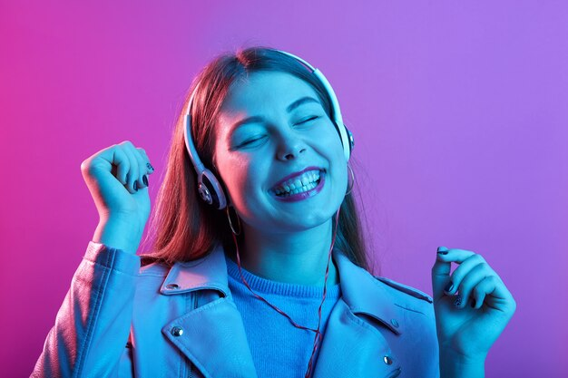 Женщина слушает музыку в наушниках, держит глаза закрытыми и счастливо улыбается, держа кулаки в изоляции над розовым неоновым пространством