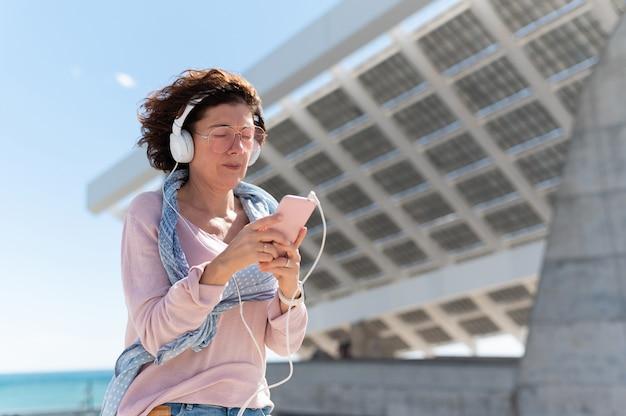 Женщина слушает музыку в наушниках и на своем мобильном телефоне