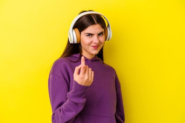 노란색에 고립 된 헤드폰으로 음악을 듣고 여자
