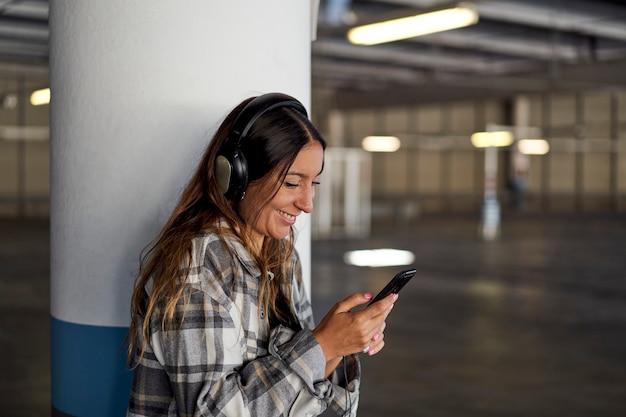 ヘッドフォンで音楽を聴いている女性。彼女は駐車場の柱にもたれかかっています。