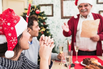 Woman listening to old man greeting at festive table
