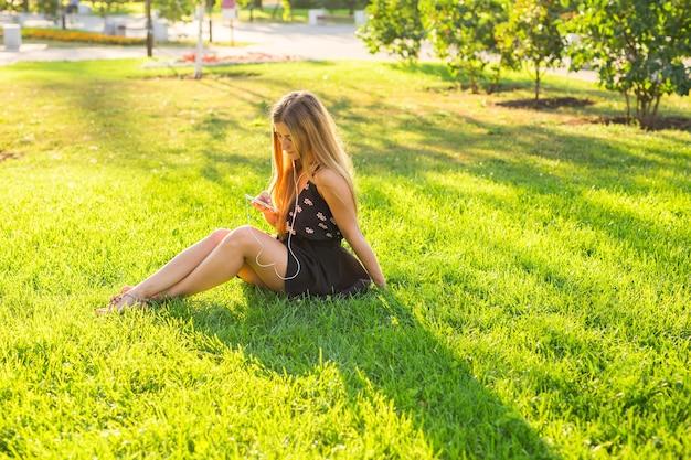 Женщина слушает музыку на траве