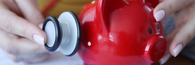 Woman listening with stethoscope to red piggy bank closeup